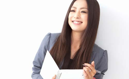 笑顔でノートとボールペンを持つ女性
