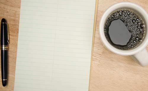 テーブルに置かれたノートとボールペンとコーヒー