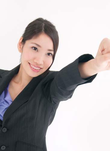 拳を突き上げやる気を見せるスーツ姿の女性