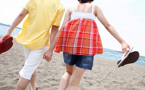 手をつなぎながら砂浜を歩くカップル