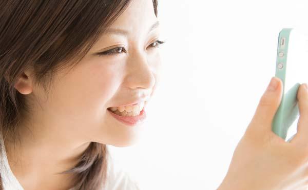 笑顔でスマフォを見つめる女性