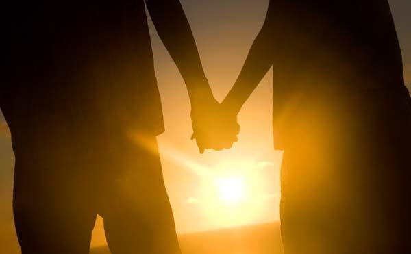 夕日に向かい手をつなぐカップル