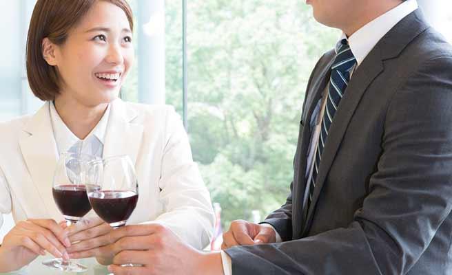 ワインを飲みながら男性と会話する女性