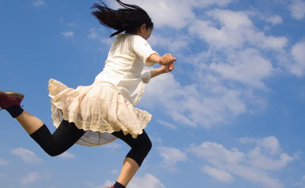 青空の元元気よく走りだす女性