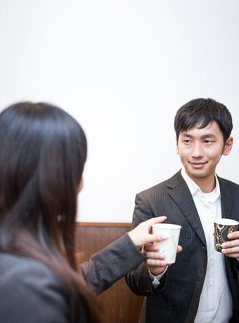 女性社員に飲み物を渡す不敵な笑顔の男性社員