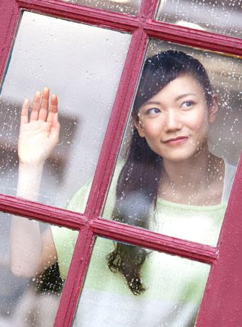 雨の日に窓から外を見てる女性