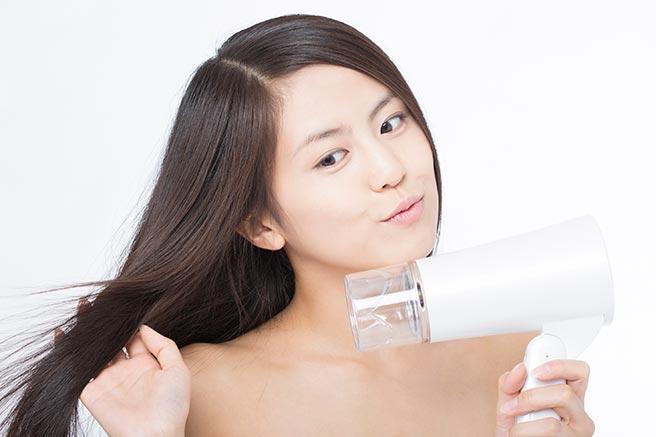 手で確認しながら髪を乾かす女性