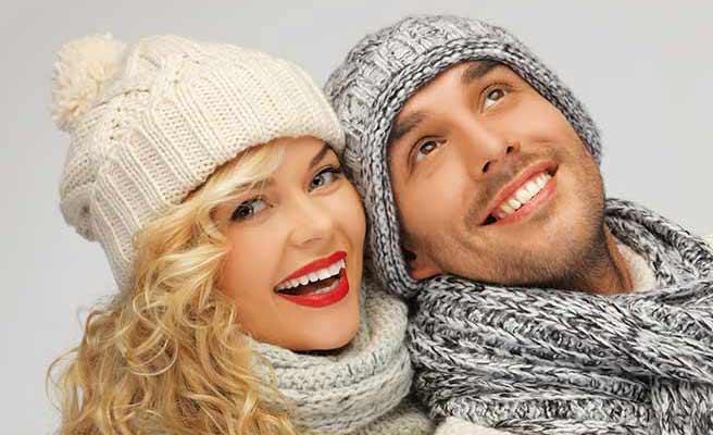 同じニットの帽子とマフラーを身に着けて並ぶカップル