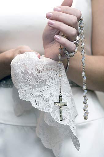 親から貰ったクロスのネックレスを持ってるウェディングドレスを着た新婦