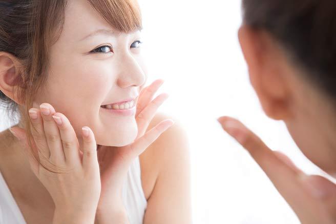 新しい出会いのために笑顔の練習をする女性