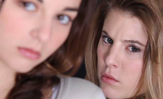 女性の背後から睨み付ける女性