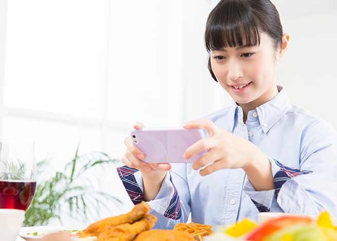 食事をスマホで撮影する女性
