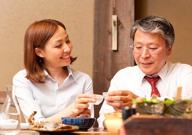 上司と日本酒を飲む気配り上手な女性