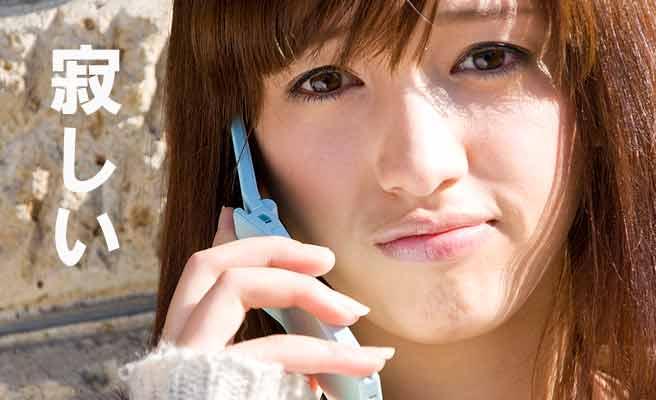 哀しい表情で電話する女性