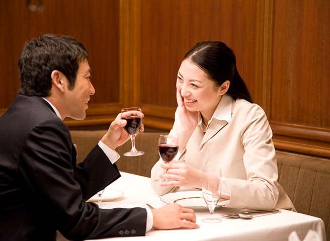 ホテルのディナーを楽しむ仕事終わりカップル