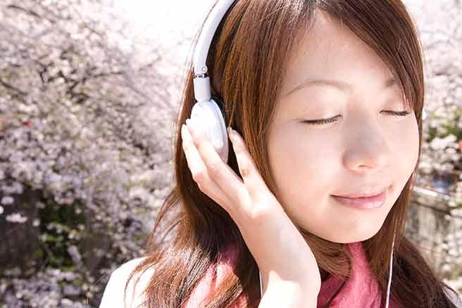 桜を見ながら失恋ソングを聞く女性