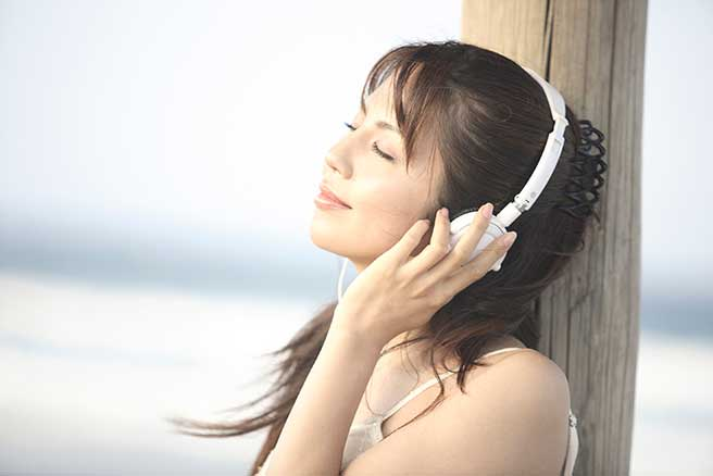 海で失恋ソングを聴く女性