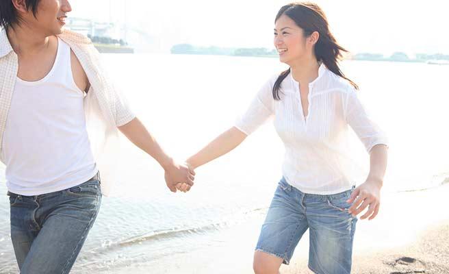海辺で手を繋いで歩くカップル