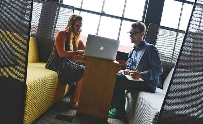 オフィスでパソコンを挟んで向い合う男女