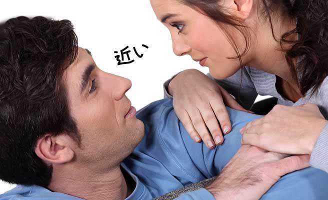 男性の肩に手をかけて顔を近づける女性
