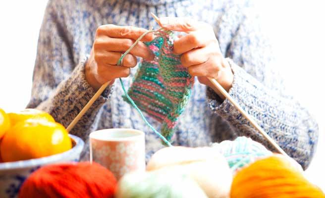 手みのマフラーを編む女性