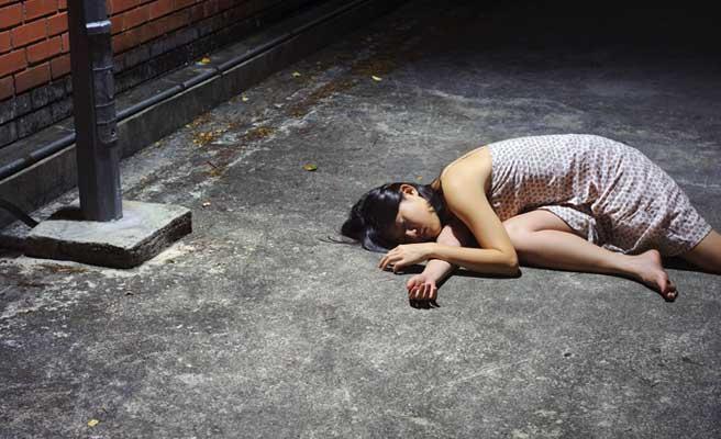 酔っ払って地面で倒れる女性