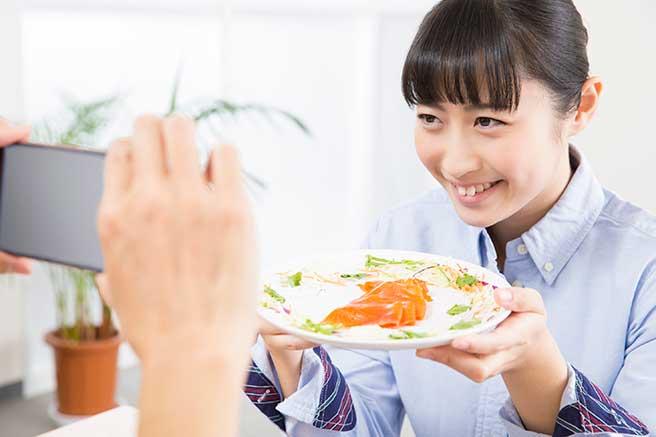 二人で一緒に食べておいしかった食事を写真にとるカップル