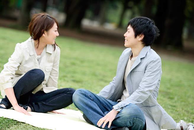 レジャーシートでまったり公園デートするカップル