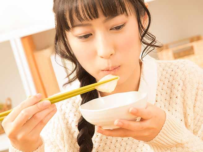 お腹が鳴らないようにゆっくりよく噛んで食べる女性