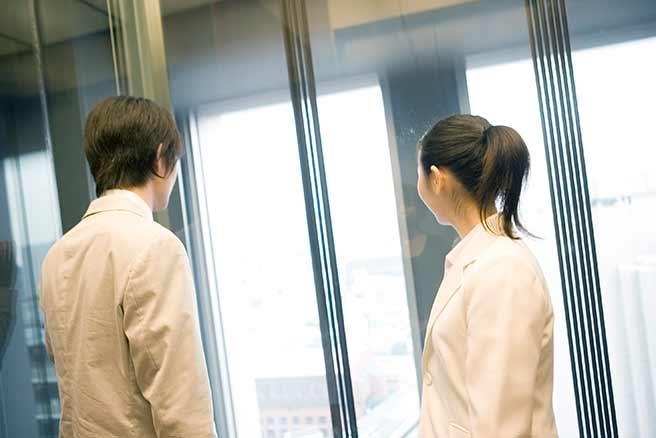 付き合ってない人と一緒にエレベーターにいる女性