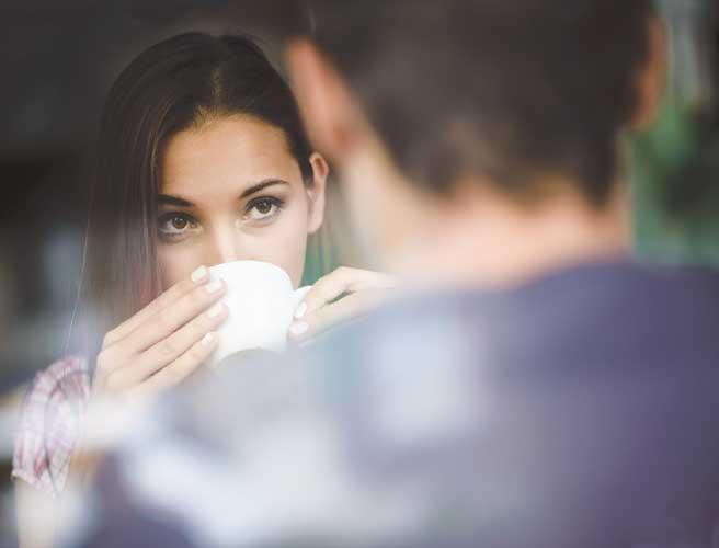 コーヒを飲みながら男を見る女性