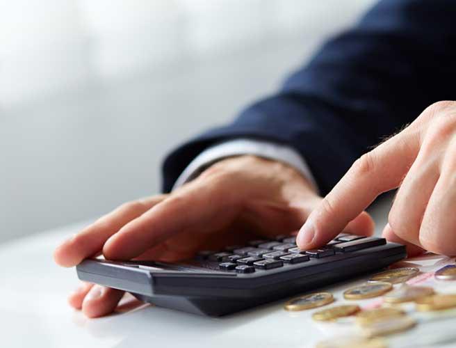 小銭と電卓をいじる男性