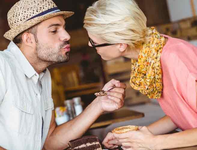 スプーンで食べる彼氏の口元を見つめる女性