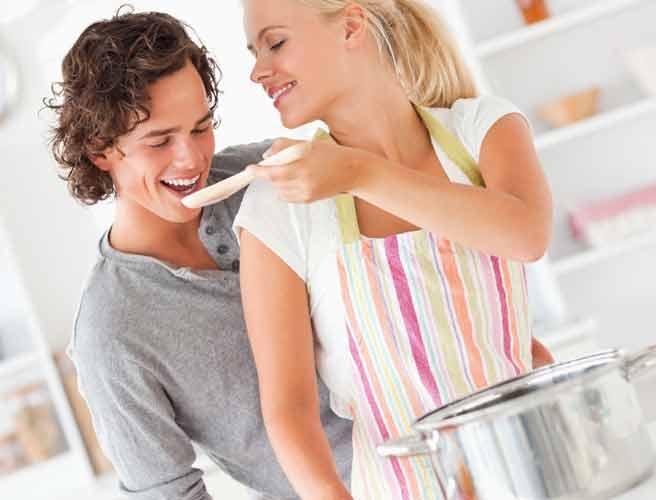 スプーンで鍋の料理を味見させる彼女に