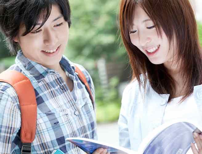 旅行先の町でガイド本を読むカップル