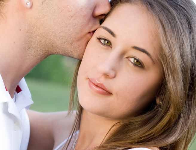 彼女のこめかみにキスする男性