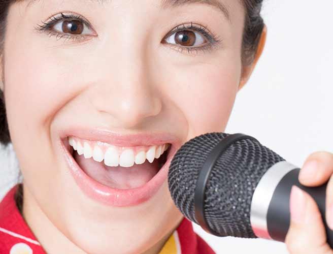 大きく口を開いて歌う女性