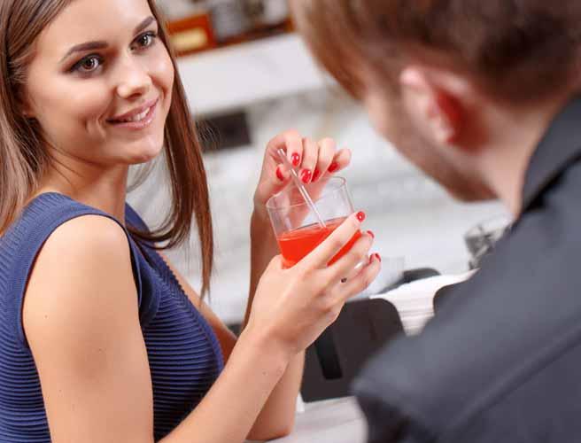 デート中、彼と会話しながらグラスを持つ女性