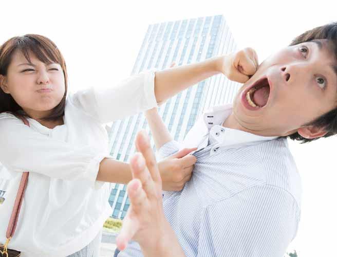 男性の顔にパンチを入れる女性