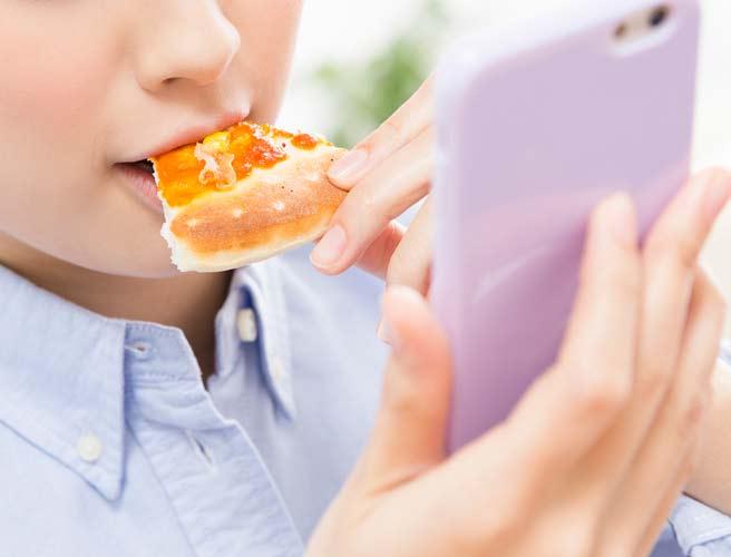 ピザを食べながらスマホを見る女性