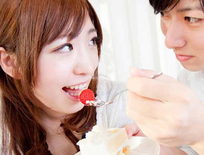ショートケーキのイチゴを彼女に食べさせようとしてる男性