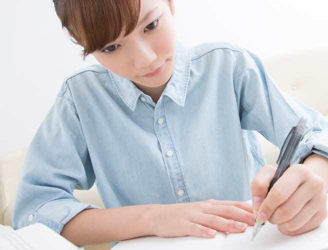 ノートに書き物をする女性