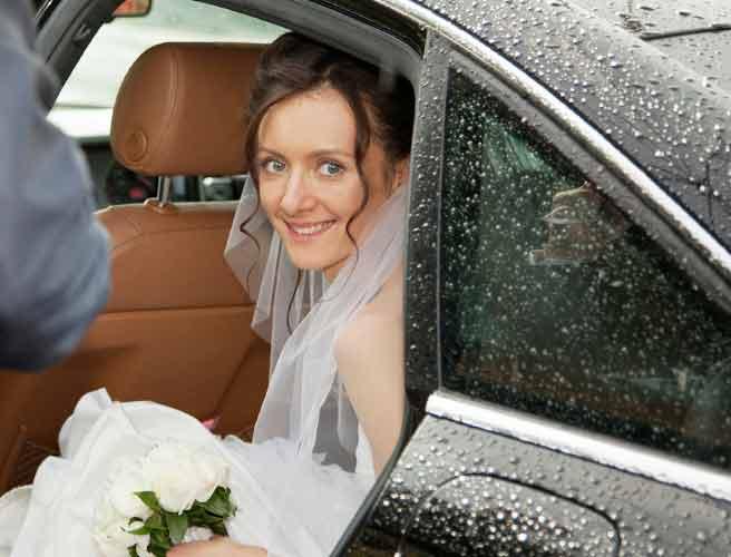雨降りのなか車から降りる新婦