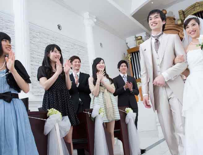 新郎新婦と結婚式に参列する人々