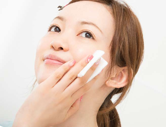 化粧水で肌の手入れをする女性