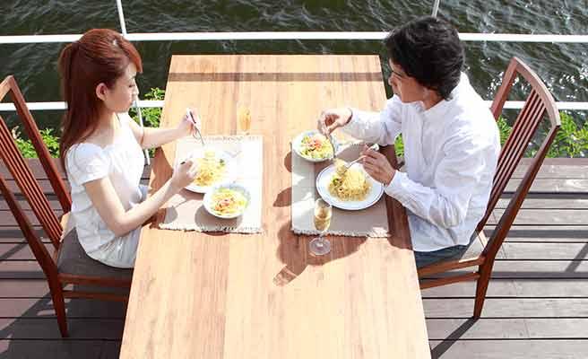 テラス席で食事するカップル