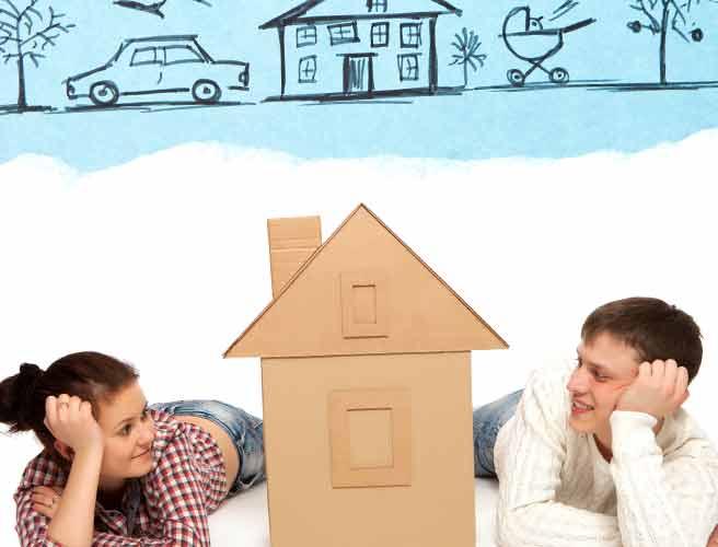 一軒屋の模型を見つめるカップル