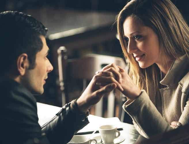 薄暗い店の中で手を繋いで見つめ合うカップル