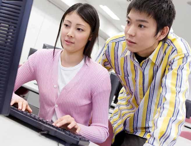 男性に教えてもらいながらパソコンを操作する女性