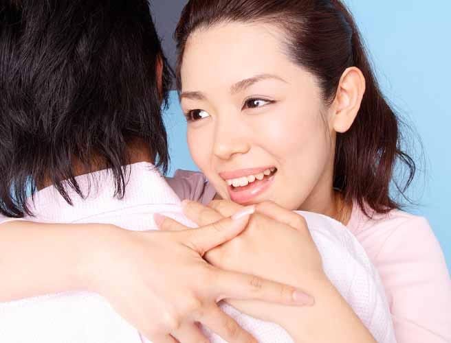男性の肩に抱きつく女性